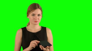 Woman with lipstick makeup looking herself in the mirror on a Green Screen