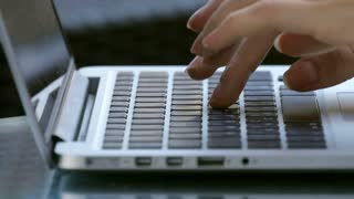 Woman working outdoor on laptop, hand on keyboard