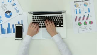 Woman's hands typing on laptop at office desk with statistics graph
