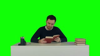 Young and concentrated student reads a book on a Green Screen