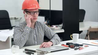 Young architect in helmet having important phone call