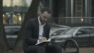 Young bearded business man thinking and wrighting notes at green park, traffic behind