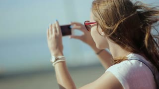 Young beatiful woman travel, sightseeing in tourist bus - happy teenage girl in sunglasses taking picture by smart phone