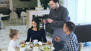 Young beautiful family have fun and dance in cafe with jolly waiter