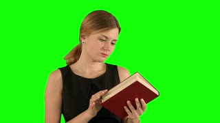 Young beautiful girl reading a book on laptop on a Green Screen, Chroma Key