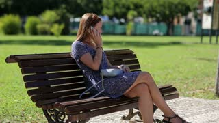 Young beautiful woman holding mobile phone in hand and sitting on the bench in the park