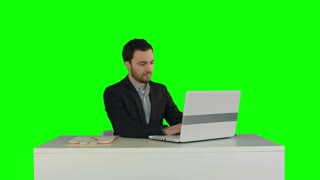 Young businessman concentrating on working with laptop computer on a Green Screen