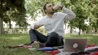 Young businessman sitting in grass and having lunch in a park summertime