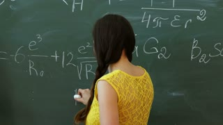 Young college student writing on the chalkboard or blackboard during a math class