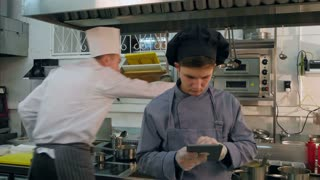 Young cook trainee using tablet while chef busy cooking in the kitchen