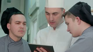 Young cook trainees having discussion with chef holding tablet