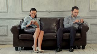 Young couple and ignoring each other looking at smartphones