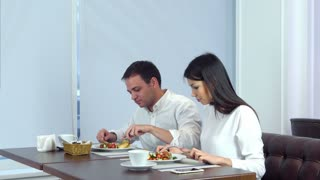 Young couple enjoying their lunch at cafe when waiter serving more food