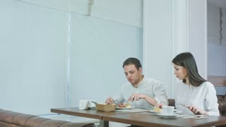 Young couple enjoying their lunch at restaurant when waiter bringing more food