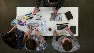Young designers working with color palette and samples at office desk