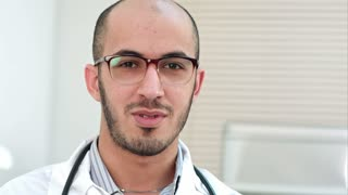 Young doctor talking and looking into the camera