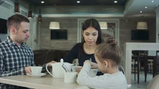 Young family in cafe. Father make a phone call while mother and daughter talking. Mother looking at him dissatisfied