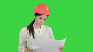 Young female architect holding blueprints and checking construction on a Green Screen, Chroma Key