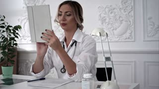 Young female doctor work on tablet computer in office
