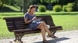 young girl sitting at the bench in a park and making notes