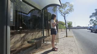 young girl waiting seating at bus stop with smart phone in blue skirt and sunglasses, summertime, and communicate