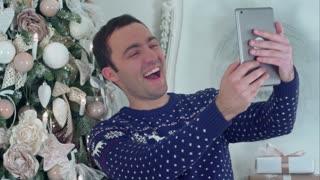Young handsome man in a Christmas knitted sweater taking selfies on a tablet