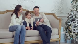 Young happy family using tablet on the sofa