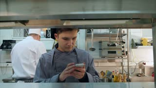 Young kitchen assistant texting on his phone during work