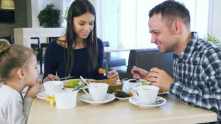 Young lovely parents feeding their blond daughter vegetable salad in cafe