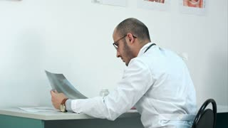 Young male doctor examining chest xray image