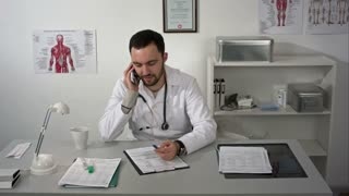 Young male doctor sits at the table in his consulting room and speaks by smartphone