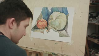 Young male student painting watercolor still life