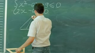 Young male teacher or student holding chalk writing on chalkboard in classroom