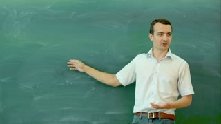 Young male teacher pointing at blank blackboard and talking