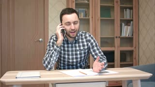 Young man arguing over the phone sitting at his desk