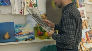 Young man hanging paintings on string in art class