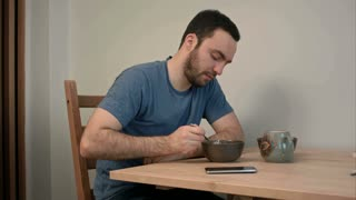 Young man having an urgent phone call in the middle of breakfast