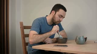 Young man having phone call in the middle of breakfast