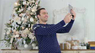 Young man in a knitted sweater taking selfies on a tablet netx to the Christmas tree