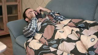 Young man pretending to be sick with flu lying on the sofa