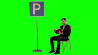 Young man reading a book near parking sign on a Green Screen