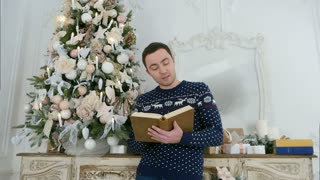 Young man reading aloud from a book standing next to the Christmas tree