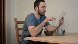 Young man reading news on tablet while eating breakfast