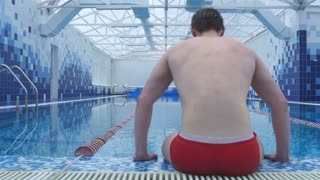 Young man sitting by the swimming pool