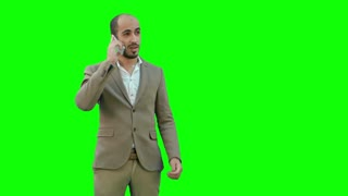 Young man talking on the phone and actively gesturing on a Green Screen, Chroma Key