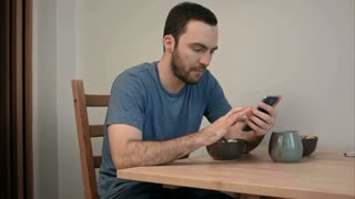 Young man using phone while eating breakfast