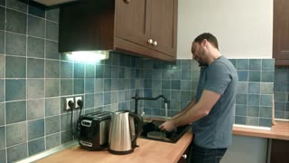 Young man washing dishes while talking on mobile phone in kitchen