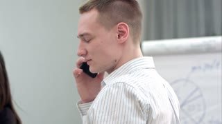 Young manager having phone call in the office