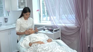 Young masseuse giving an attractive woman facial massage at beauty spa