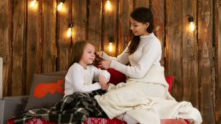 Young mother in white sweater plaiting her daughter hair